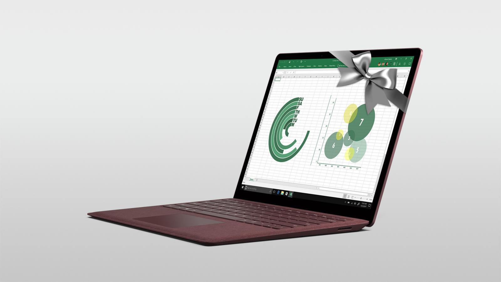Surface Laptop in Burgundy wrapped in a silver bow with Excel shown on the screen.
