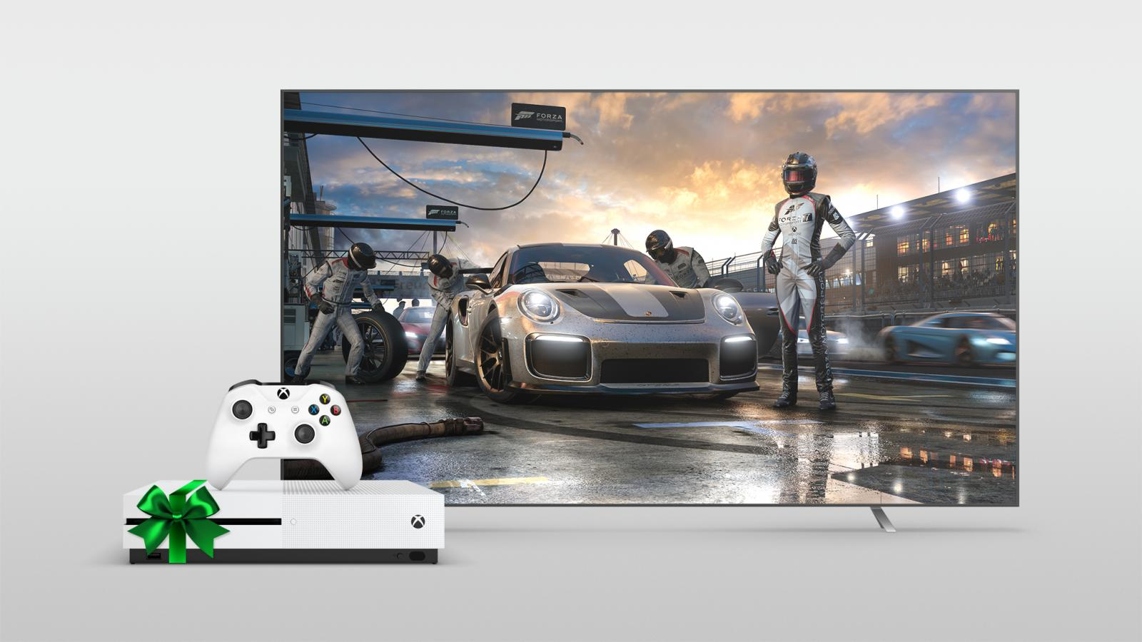 Xbox One S wrapped in a green bow next to a large TV with Forza shown on the screen